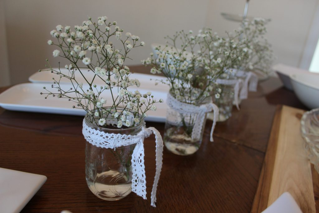 Inexpensive baby's breath in mason jars with a little bit of lace is the perfect {inexpensive} compliment to a rustic shower